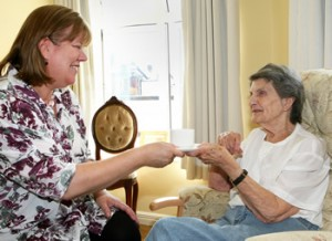 Image of lady in nursing home talking to carer (Simon Emery @ SEA Photography)